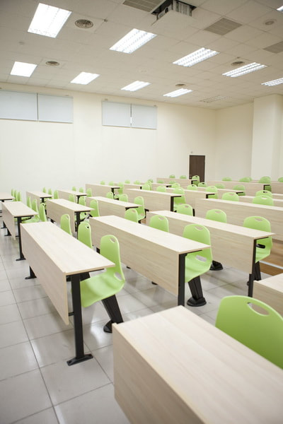 training room with auto-return green plastic chairs and fix table