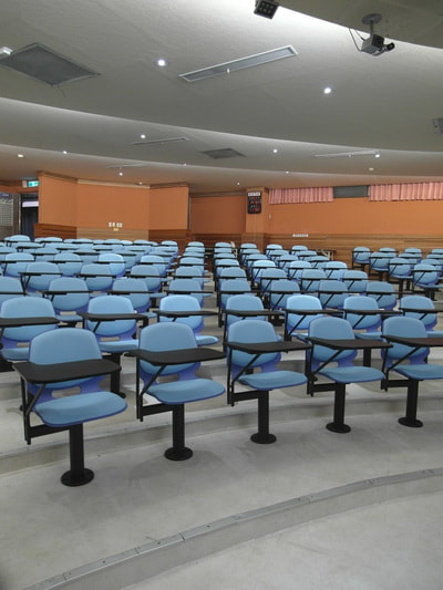 Fix chair blue plastic and light blue fabric with writing tablet for auditorium room